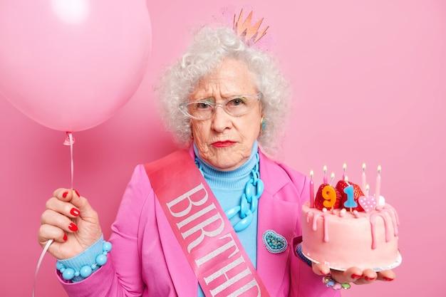Portret poważnej babci świętującej 91 urodziny trzyma pyszne ciasto z płonącymi świecami napompowany balon ubrana w świąteczny strój wygląda smutno, jakby się starzała