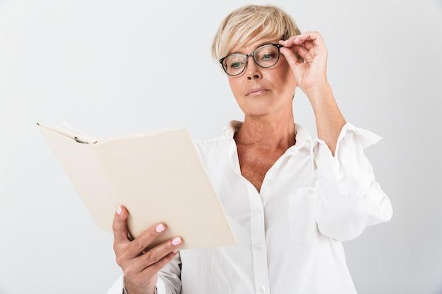 Portret poważnej dorosłej kobiety noszącej okulary czytające książkę na białym tle nad białą ścianą w studio