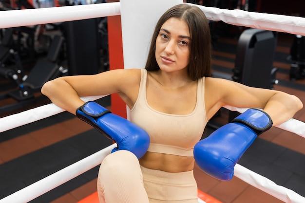 Portret poważnej dziewczyny siedzącej na ringu bokserskim w rękawiczkach