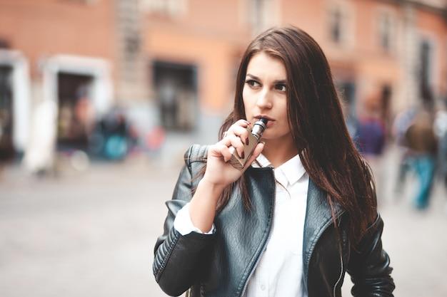 Portret poważnej kobiety, która używa elektronicznego papierosa w celu zmniejszenia stresu