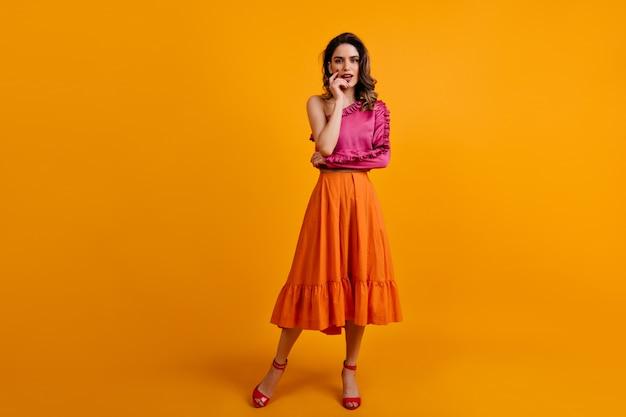 Portret poważnej kobiety nosi długą pomarańczową spódnicę