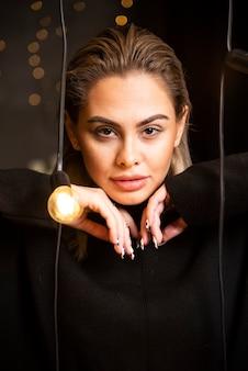 Portret poważnej kobiety w czarnym swetrze stojąc i pozowanie