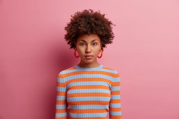 Portret poważnej, kręconej, pięknej młodej kobiety o spokojnym wyrazie twarzy, ma pewny siebie wygląd, ubrana w sweter w paski z długimi rękawami, odizolowany na różowej ścianie. bez emocji