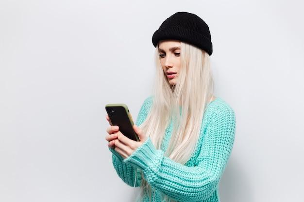 Portret poważnej ładnej blondynki patrzącej w smartfonie