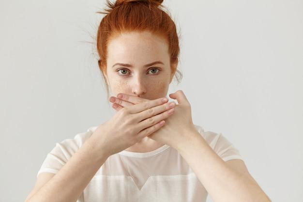 Portret poważnej młodej kobiety europejskiej imbir obejmujące usta obiema rękami z zachowaniem tajemnicy. piegowata ruda kobieta w bluzce nie chce rozpowszechniać plotek ani jakichś poufnych informacji