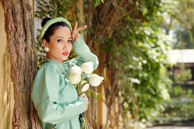Portret poważnej młodej wietnamki stojącej przy drzewie z bukietem kwiatów lotosu w rękach i patrzącej na kamerę