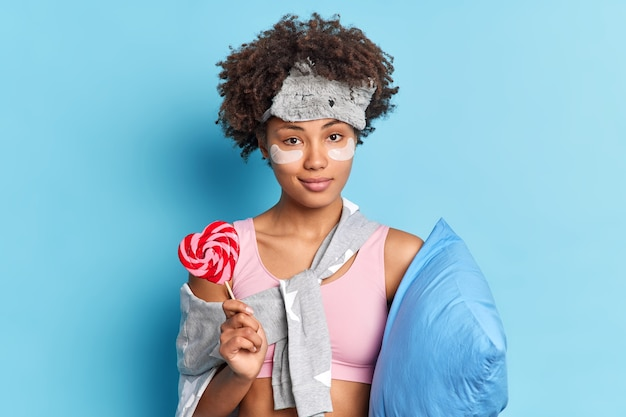 Portret poważnej pewnej siebie pięknej kobiety trzymającej słodkie cukierki na patyku budzi się po zdrowym śnie ubrana w nocną pozę z poduszką na niebieskiej ścianie