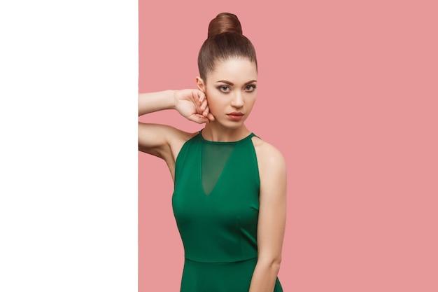 Portret poważnej pięknej młodej kobiety z fryzurą kok, makijaż w zielonej sukience stojącej w pobliżu białej ściany, dotykając jej twarzy i patrząc na kamery. kryty strzał studio, na białym tle na różowym tle.