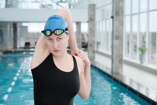 Portret poważnej sportowej młodej kobiety w czapce i okularach rozciągających ramię przed treningiem pływackim