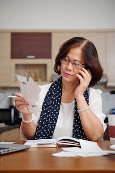 Portret poważnej starszej kobiety rozmawiającej przez telefon i sprawdzającej rachunki za media, gdy siedzi przy kuchennym stole