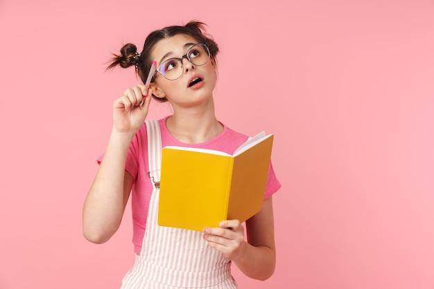 Portret poważnej uroczej dziewczyny w okularach trzymającej zeszyt i myślącej na białym tle nad różową ścianą