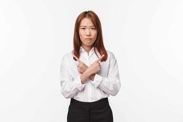 Portret poważnie niezadowolonej niezdecydowanej azjatyckiej kobiety w białej koszuli, wskazującej bokiem z rękami skrzyżowanymi w lewo i prawo, rozczarowany i zirytowany, biała ściana