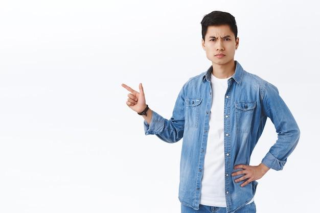 Portret poważnie wyglądającego gniewnego młodego azjatyckiego faceta besztającego osobę za popełnienie wielkiego błędu, wskazującego palcem w lewo na coś niepokojącego i złego, marszczącego brwi i mrużącego oczy osądzającą, białą ścianę