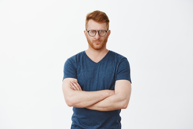 Portret poważnie wyglądającego przystojnego dojrzałego mężczyzny z włosiem w fajnych okularach, wpatrującego się, trzymającego kciuki na piersi