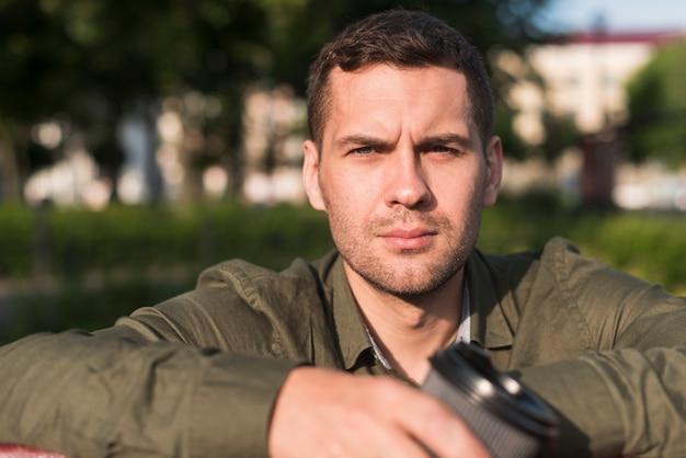 Portret poważny młody człowiek patrzeje kamerę przy parkiem