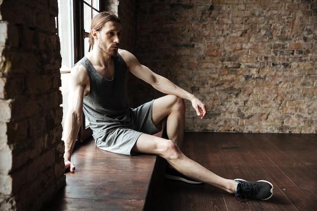 Portret poważny młody człowiek w sportswear odpoczywać