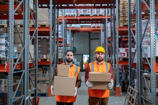 Portret poważnych pracowników magazynowych w pomarańczowych kamizelkach stojących ze stosami pudeł w przejściu między półkami z metalowej ramy