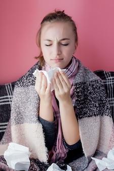 Portret poziomy młoda dziewczyna z chusteczką i katar w profilu, kichanie z grypy, biała skóra modelki na różowej ścianie. pojęcie opieki zdrowotnej i medycznej.