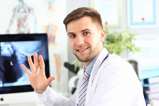 Portret pozuje w szpitalnym gabinecie uśmiechnięty doc. uśmiechnięty chirurg noszenie medycznych płaszcz. zdjęcie rentgenowskie ciała na wyświetlaczu komputera.