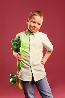 Portret pozuje z deskorolka młoda chłopiec