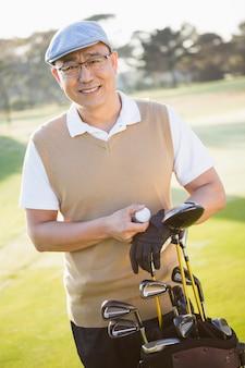 Portret pozuje z jego golfowymi wyposażeniami golfista