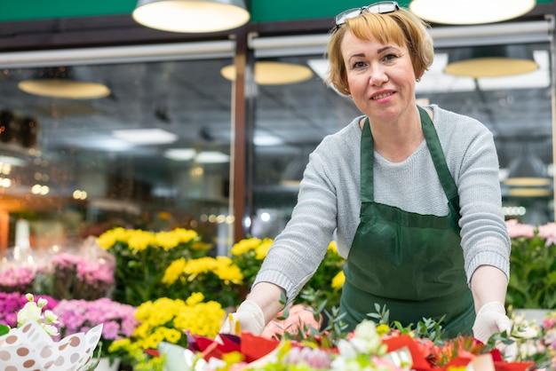Portret pozuje z kwiatami dojrzała kobieta