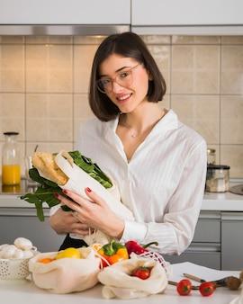 Portret pozuje z sklepami spożywczymi szczęśliwa kobieta