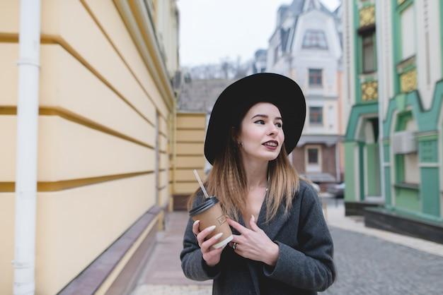 Portret pozytywna dziewczyna z filiżanką napoje w ona ręki