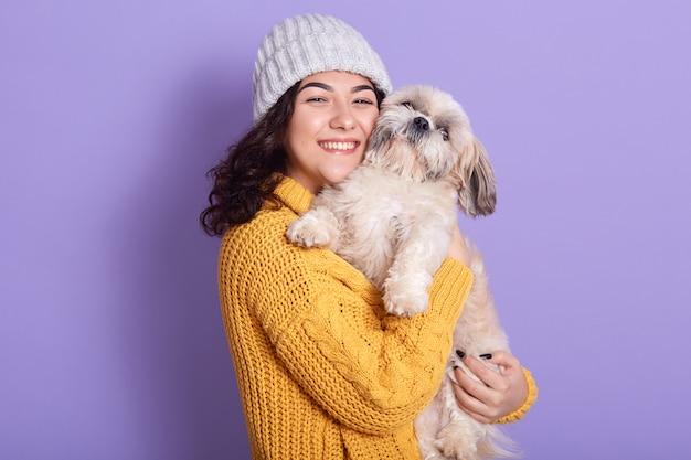 Portret pozytywna szczęśliwa brunetka trzyma jej białego zwierze domowy