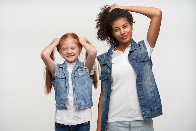 Portret pozytywne młode panie w kamizelkach dżinsowych i białych koszulach, trzymając długie włosy z uniesionymi rękami z lekkim uśmiechem, na białym tle