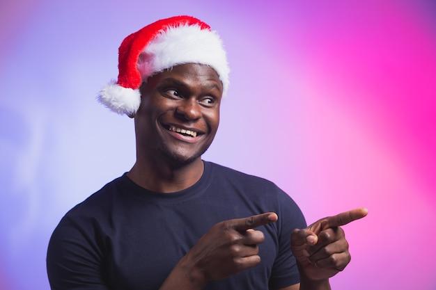 Portret pozytywnego afroamerykańskiego uśmiechniętego mężczyzny w santa hat i casualowej koszulce na kolorowym