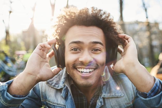 Portret pozytywnego ciemnoskórego dorosłego mężczyzny, uśmiechającego się szeroko, siedząc w parku, słuchając muzyki w słuchawkach i trzymając je rękami, aby lepiej słyszeć.