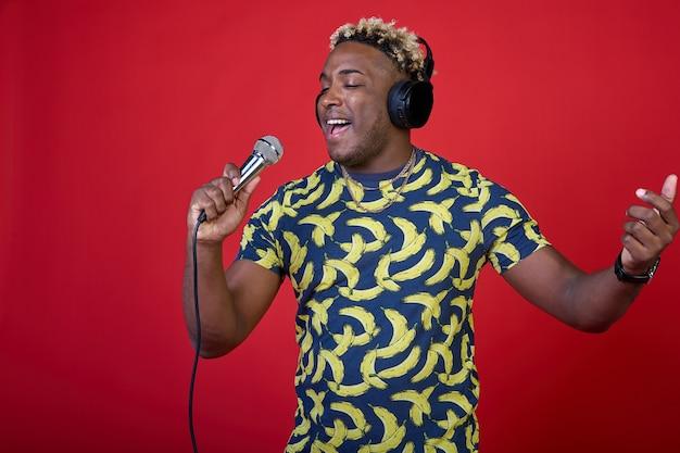 Portret pozytywnego cieszącego się pięknym afrykańskim mężczyzną z mikrofonem i słuchawkami na głowie