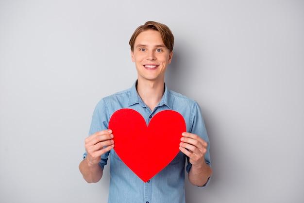 Portret pozytywnego czarującego faceta posiadają znak serca duży czerwony papier