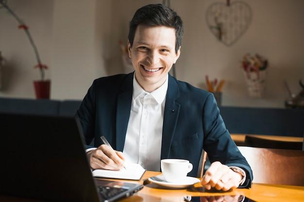 Portret pozytywnego menedżera dorosłych kaukaski siedzi w swoim miejscu pracy, popijając kawę z uśmiechem.