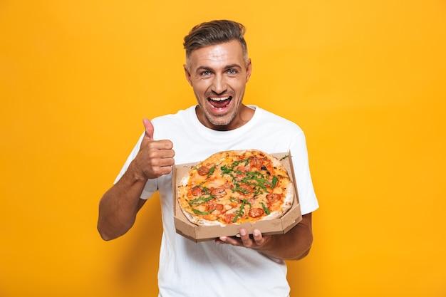 Portret pozytywnego mężczyzny w wieku 30 lat w białej koszulce, trzymającego i jedzącego pizzę, stojąc odizolowanego na żółto