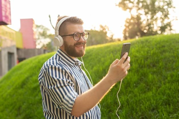 Portret pozytywnego młodzieńca z wąsami i brodą, słuchając audiobooka podczas spaceru po parku. koncepcja uczenia się wypoczynku.