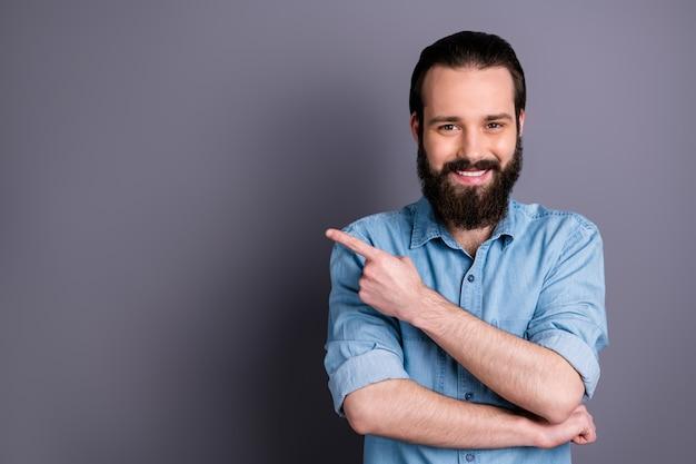 Portret pozytywnego, pewnego siebie fajnego faceta promotor wskazujący palec wskazujący copyspace przedstawia reklamy promocyjne porady dotyczące wyboru nosić dobre ubrania wyglądające na białym tle na szarej ścianie