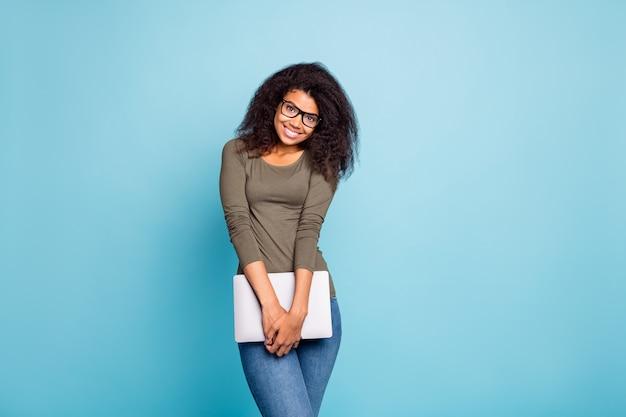 Portret pozytywnego profesjonalnego menedżera afroamerykańska kobieta trzyma laptopa słodki dziewczęcy przedsiębiorca gotowy do pracy nosić swobodny styl zielony strój dżinsy dżinsowe izolowane na niebieskiej ścianie