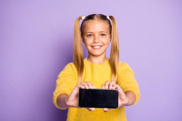 Portret pozytywnego uroczego dziecka trzymaj telefon komórkowy, aby selfie podczas podróży nosić sweter w stylu swobodnym izolowany na fioletowej ścianie