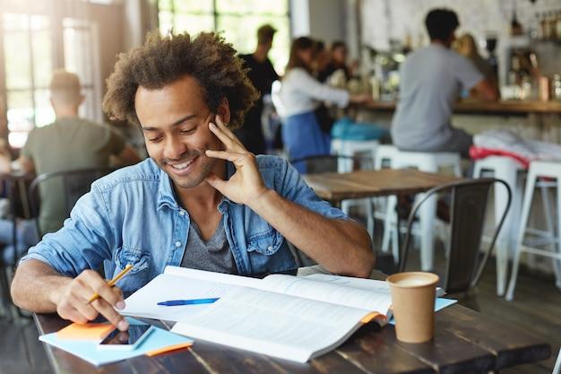 Portret pozytywnego uśmiechniętego studenta afro american college'u w talii, piszącego wiadomość tekstową na swoim smartfonie z pustym ekranem miejsca kopiowania, siedząc w stołówce i pracując nad zadaniem domowym