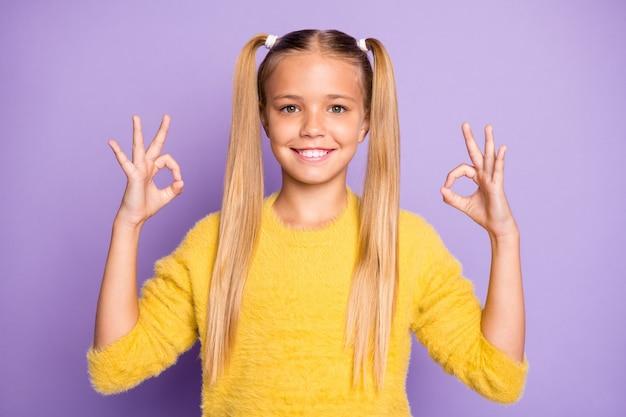 Portret pozytywnego, wesołego, fajnego dziecka, przyszłego promotora, pokaż w porządku znak polecam reklamy wybierz porady sprzedażowe nosić żółty sweter odizolowany na fioletowej ścianie