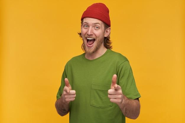 Portret pozytywnego, wesołego mężczyzny z blond fryzurą i brodą. ubrana w zieloną koszulkę i czerwoną czapkę. ma tatuaż. wskazuje na ciebie palcami. pojedynczo na żółtej ścianie