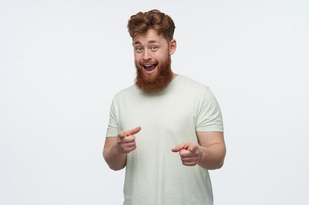 Portret pozytywnego, wesołego mężczyzny z dużą brodą i rudymi włosami nosi pustą koszulkę, wskazując palcem na ciebie