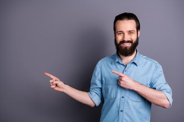 Portret pozytywnego, wesołego, pewnego siebie faceta promotor wskazujący palec wskazujący miejsce na kopię zademonstrować reklamy obecne promocyjne nosić dobry wygląd strój na białym tle na szarej ścianie