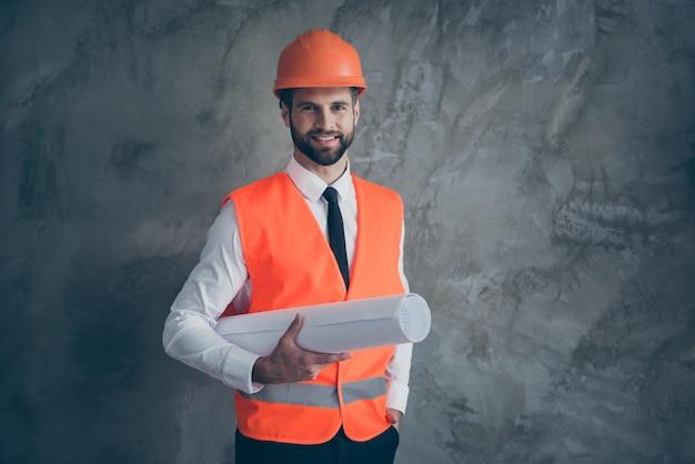 Portret pozytywnej architektury zawodowej konstruktora trzymającego swój plan budowy budynku nosić mundur pomarańczowy kask na białym tle na szarej ścianie