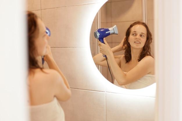 Portret pozytywnej atrakcyjnej kobiety suszącej włosy przed lustrem, mającej pozytywne emocje, patrzącej na siebie z uśmiechem, trzymającej w rękach suszarkę do włosów.