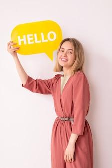 Portret pozytywnej atrakcyjnej młodej kobiety w różowym kombinezonie pokazując tag komunikacyjny mówiąc hello