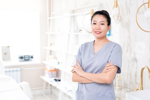 Portret pozytywnej azjatyckiej kosmetyczki w średnim wieku w zarośla stojącej ze skrzyżowanymi rękami w gabinecie kosmetycznym o współczesnym designie