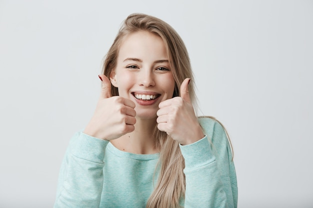 Portret pozytywnej blondynki żeńska kobieta z szerokim uśmiechem i aprobatami